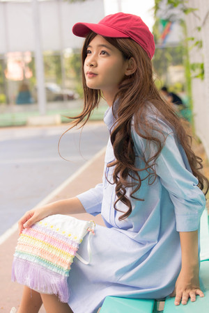 Portrait of thai teen beautiful girl blue dress red hat happy and relax