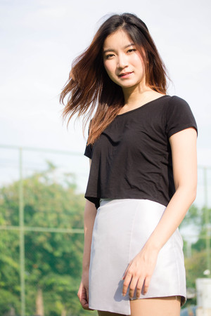 portrait of thai beautiful young adult, relaxed and smile in tennis court