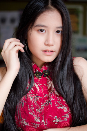 Portrait of thai teen beautiful girl in Chinese dress, relax and smile.