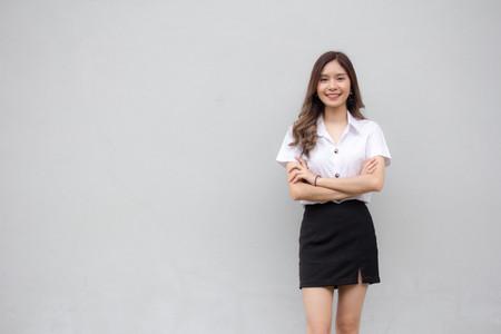 タイの成人学生の制服美少女の肖像画はリラックスして笑顔