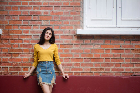 Portrait of thai Jeans skirt yellow shirt adult beautiful girl relax and smile