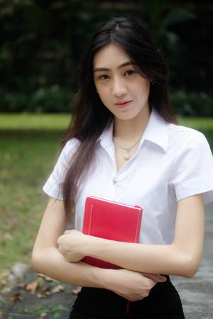 Portrait of thai adult student university uniform beautiful girl read red book