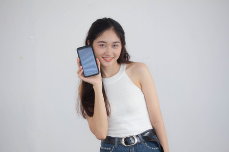 Portrait of thai china adult beautiful girl White shirt blue jeans show her smart phone