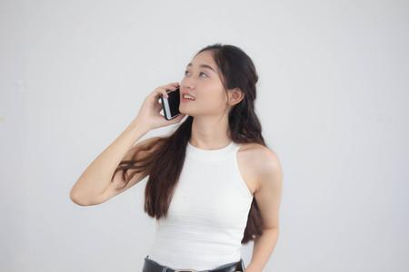 Portrait of thai china adult beautiful girl White shirt blue jeans calling smart phone 写真素材