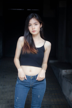 Portrait of thai china adult beautiful girl black shirt blue jeans relax and smile