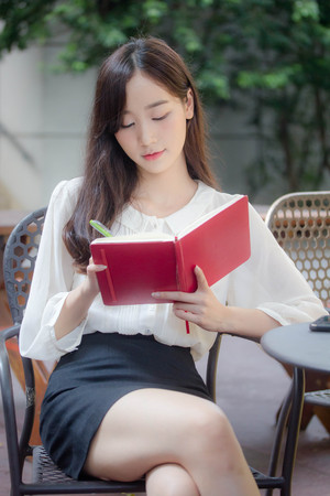 portrait of thai china adult office girl white shirt Write book Banco de Imagens - 121750106