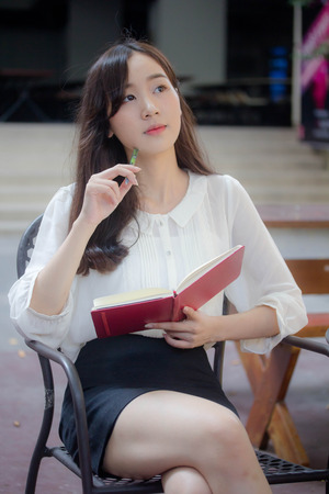 portrait of thai china adult office girl white shirt Write book