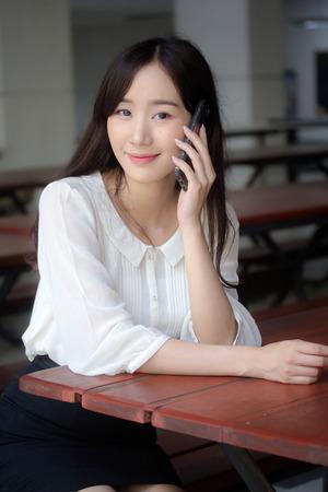 portrait of thai china adult office girl white shirt walk  and calling smart phone 版權商用圖片