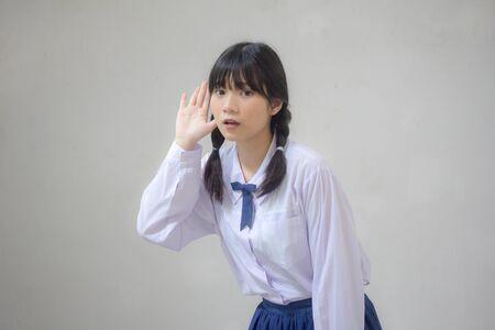 Portrait of thai high school student uniform beautiful girl listen Banco de Imagens