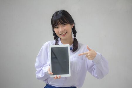 Portrait of thai high school student uniform beautiful girl show tablet