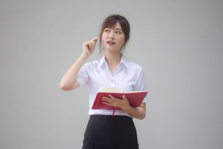 Portrait of thai adult student university uniform beautiful girl Write book