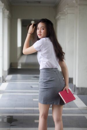 thai adult student university uniform beautiful girl walk relaxed and smile.