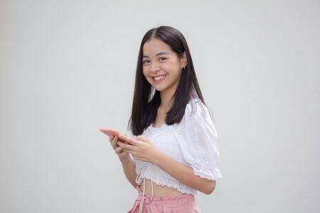asia thai japanese teen teen White t-shirt beautiful girl using her phone and smile