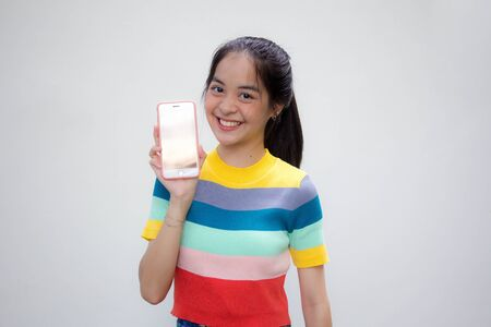 asia thai teen color t-shirt beautiful girl show her phone and smile Фото со стока