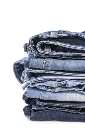 White background denim blue jeans stack. Clothes, fashion, charity