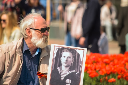 regiment: An elderly man with a portrait of a relative to the Immortal regiment Editorial