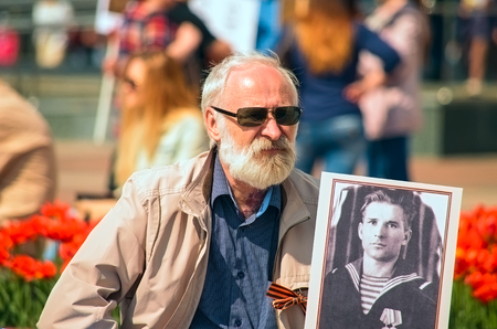 annexation: ULYANOVSK, RUSSIA - MAY 9, 2016: White-bearded old man with a portrait of a relative to the Immortal regiment. May, 9, 2016 in Ulyanovsk city, Russia.