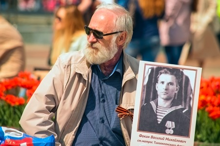 ULYANOVSK, RUSSIA - MAY 9, 2016: White-bearded old man with a portrait of a relative to the Immortal regiment. May, 9, 2016 in Ulyanovsk city, Russia.