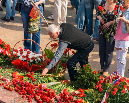 ULYANOVSK, RUSSIA - MAY 9, 2016: ULYANOVSK, RUSSIA - MAY 9, 2016: People with flowers at the Eternal Fire.. May, 9, 2016 in Ulyanovsk city, Russia.