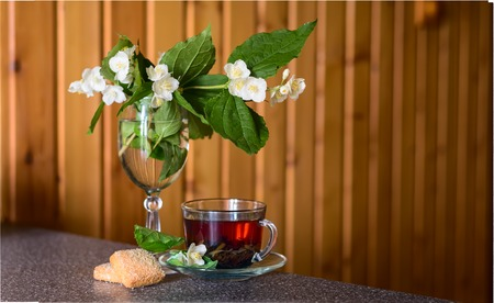Black tea with jasmine blossom in a glass cup on the brown wooden background. Copy space background. Stock Photo
