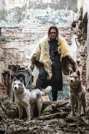 A young man in a leather cloak and a fur cape hides with two dogs in a ruined building. Stock Photo