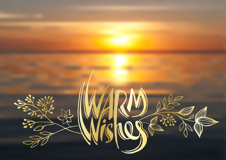 Warm wishes, vector lettering, handwritten golden text and floral elements on blurred background of sea sunset.