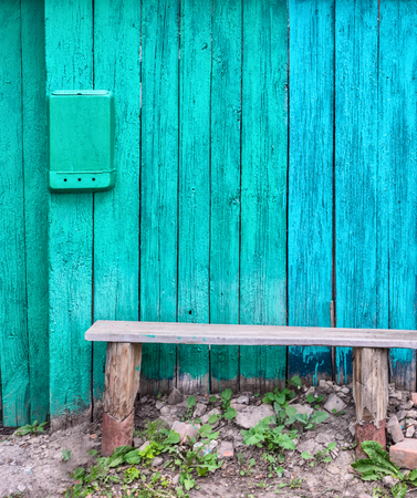 A typical wooden bench standing against the background of a blue wooden wall in the Russian outback. Tradition, country style.