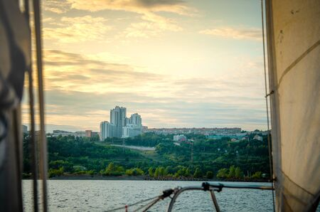 Ulyanovsk, Russia - July 20, 2019. View of the city of Ulyanovsk from the side of a sailboat with rigging and sails. Editöryel