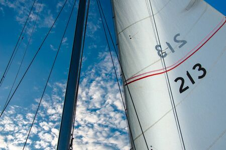 Snow-white sails against a clean bright blue sky on a sunny summer day Stock Photo