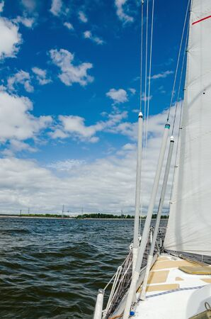 View of the water and the distant shore from the side of a sailboat with rigging and sails