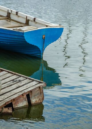 The stern of an old wooden boat moored at the pier, and reflection Фото со стока