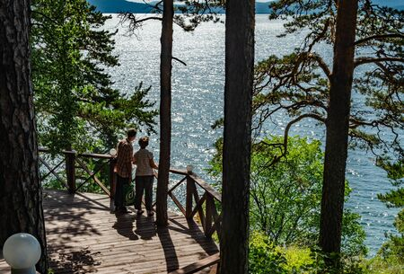 Photo of a sunny summer day where two travelers stand on a wooden observation deck and admire Lake Turgoyak among the mountain hills in the forest