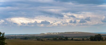 Photo of a summer landscape with fields and chalk hills.