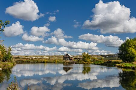 Photo of a lonely wooden house on the lake, which reflects summer clouds against the backdrop of chalk hills.