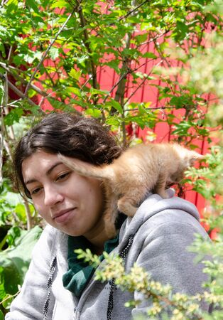Photo of a girl with a red kitten on her shoulder