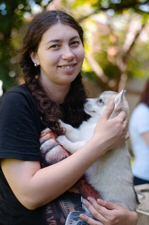 Photo of a girl and a husky puppy in her arms Banco de Imagens