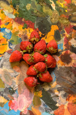 ripe red strawberries on colorful oil paint palette.
