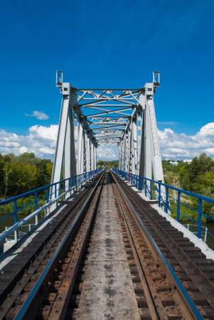 Railroad bridge view on background with green trees and blue cloudy sky