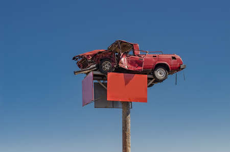 Broken red car on an advertising pole, blue sky background Фото со стока
