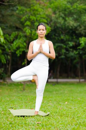vriksasana: Beautiful woman practicing yoga in the park, Tree Posture,Vriksasana