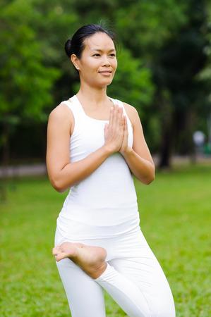 vriksasana: Beautiful woman practicing yoga in the park,Tree Posture,Vriksasana Stock Photo