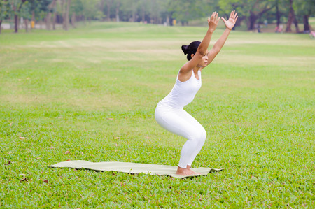 Beautiful woman practicing yoga in the park. Chair Pose, Utkatasana.