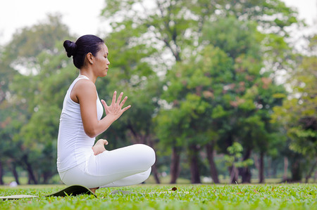 padma: Beautiful woman practicing yoga in the park.Half Lotus Toe Balance  Pandangustha Padma Utkatasana.