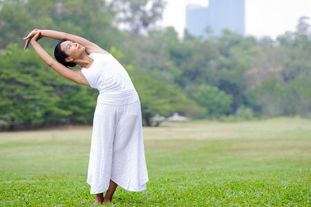 Beautiful woman practicing yoga in the park.Half Moon Pose  Ardha Chandrasana