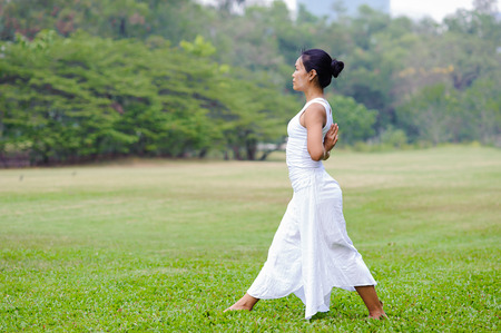Beautiful woman practicing yoga in the park.Namaste & Anjali Mudra.