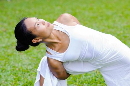 parsvakonasana: Beautiful woman practicing yoga in the park.Extended Side Angle Pose  Utthita Parsvakonasana. Stock Photo
