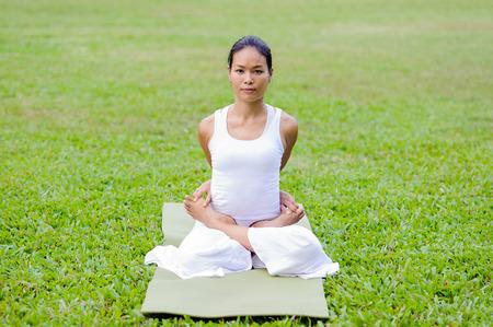 baddha: Beautiful woman practicing yoga in the park.The Locked Lotus Pose  Baddha Padmasana. Stock Photo