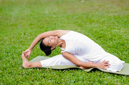 janu: Beautiful woman practicing yoga in the park.Revolved Head to Knee Pose  Parivrtta Janu Sirsasana.
