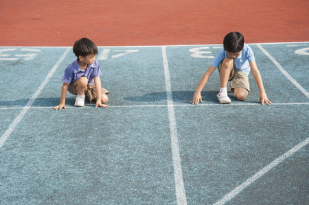 Two boys run competition on the green track