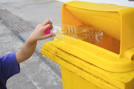Children hand dropping used bottle in the yellow trash